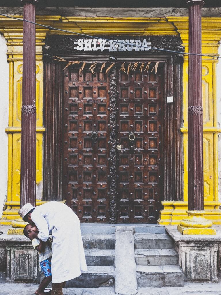 An older brother embraces his younger infront of a classic Zanzibar door